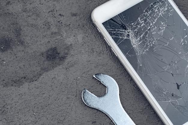 Smartphone estrellado con herramientas de reparación sobre fondo gris