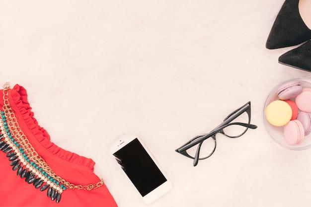 Smartphone con falda, gafas y macarrones.