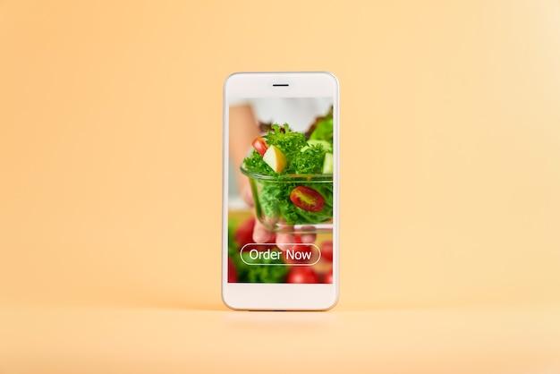 Smartphone en el fondo naranja y muestra la pantalla de la aplicación para pedir ensaladas en línea.
