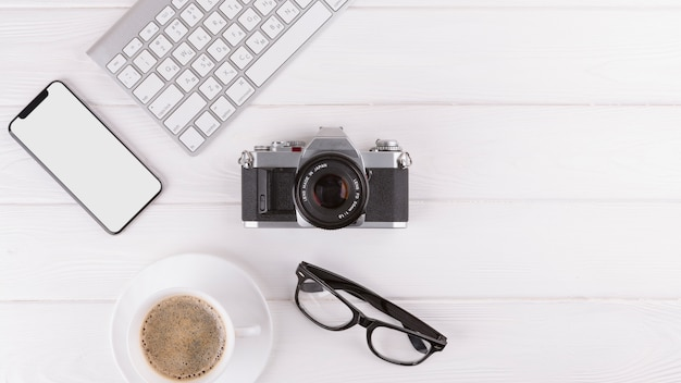 Smartphone, gafas, cámara, taza y teclado.