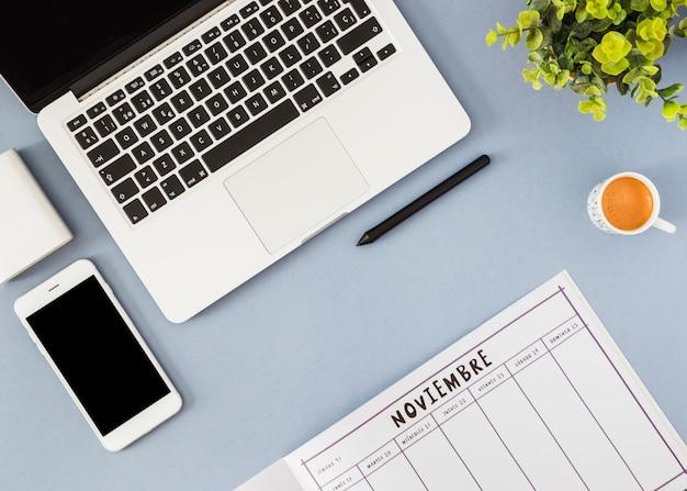 Smartphone y laptop con notebook en mesa azul