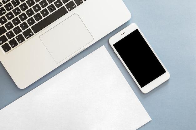 Smartphone con laptop y papel en blanco.