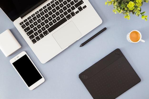 Smartphone con laptop, taza de café y notebook.