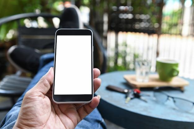 Smartphone en la mano, la espalda es el café en la mesa.