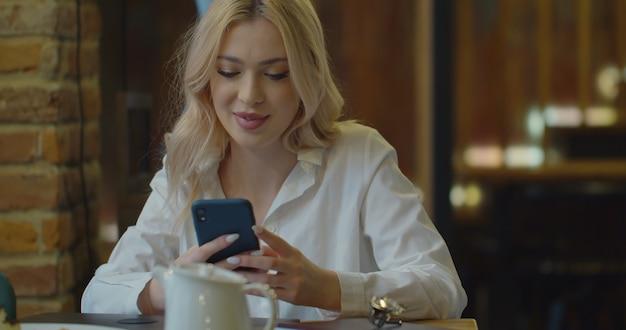 Smartphone en manos femeninas en café, utilizando el sitio web de navegación de sms de mensajes de texto de teléfono móvil.
