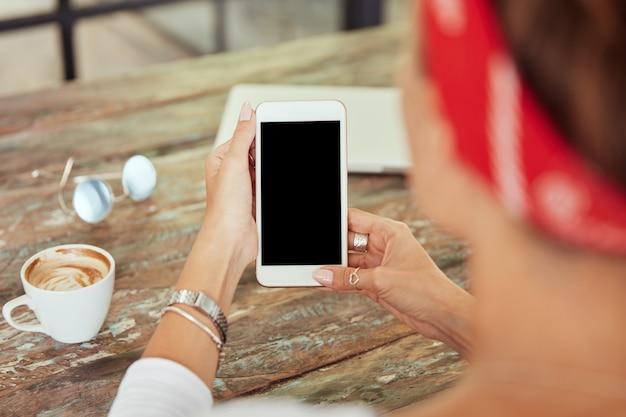 Smartphone en manos de mujer en café