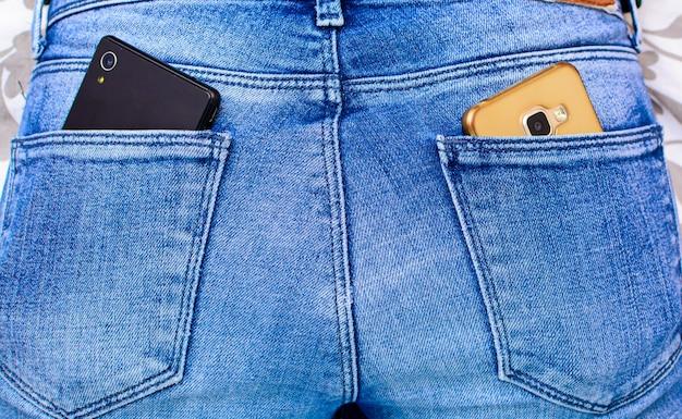 Smartphone negro en el bolsillo trasero de jeans de niña