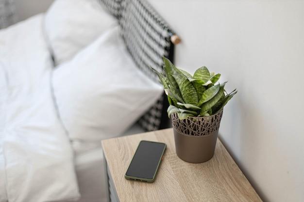 Smartphone negro en la mesita de noche. planta verde en una maceta sobre la mesa en el dormitorio