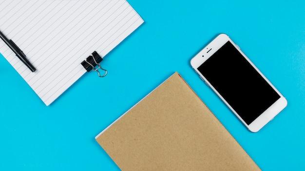 Smartphone con notebook en mesa