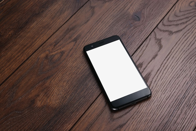 Smartphone con pantalla blanca en el fondo de maqueta de mesa de madera.