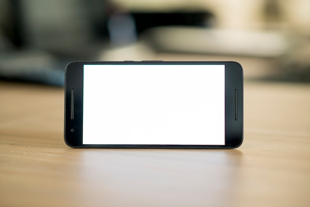 Smartphone con pantalla en blanco en blanco sobre el escritorio de madera
