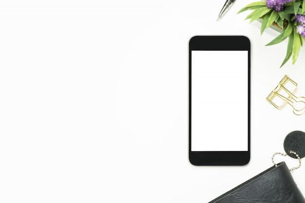 Smartphone con pantalla en blanco está encima de la mesa blanca. vista superior con copyspace, endecha plana.