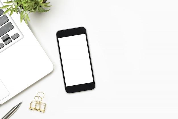 Smartphone con pantalla en blanco está encima de la mesa blanca.