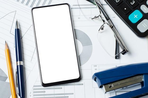 Smartphone con pantalla en blanco en el fondo de gráficos y tablas. copie el espacio. el concepto de inversión en línea o comercio de acciones o negocios.