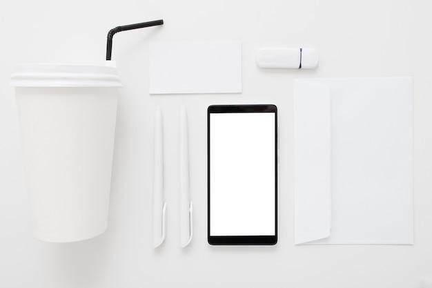 Smartphone con pantalla en blanco y material de oficina