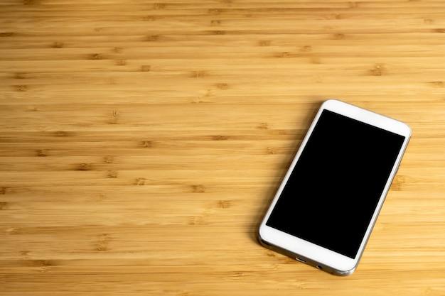 Smartphone con pantalla en blanco en la mesa de madera de bambú en la oficina