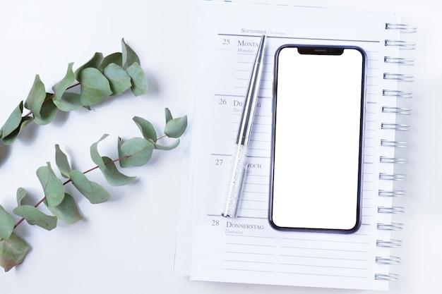 Smartphone con pantalla en blanco en un portátil