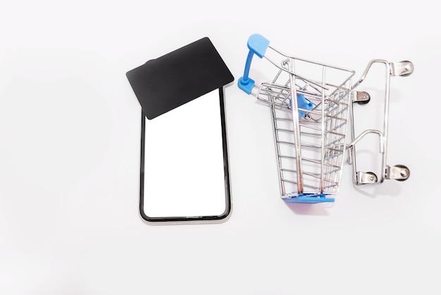 Smartphone con pantalla en blanco y una tarjeta de crédito negra en la parte superior, y un carrito de compras sobre fondo blanco.