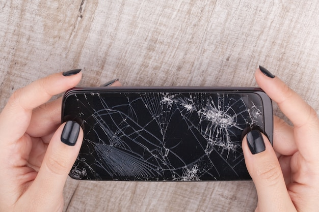 Smartphone con pantalla rota en la mano de la niña.