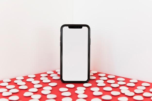 Smartphone con pequeños corazones en mesa