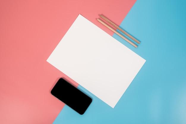 Smartphone y plantilla de papel en blanco en papel de dos colores con azul y rosa de fondo.