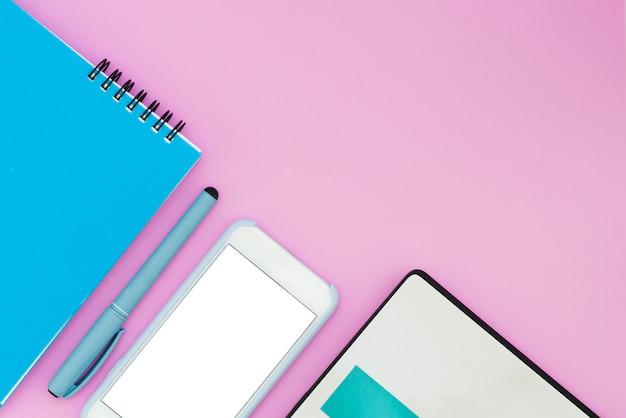 Smartphone, portátil y portátil sobre un fondo rosa. vista superior. espacio de trabajo flat la layout