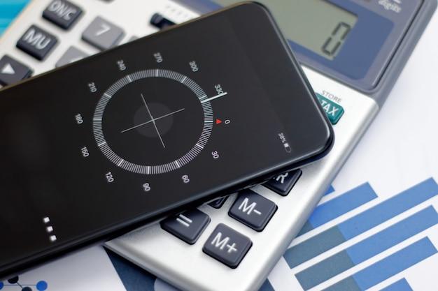 Smartphone que muestra la brújula en la calculadora. datos financieros y concepto de tecnología.