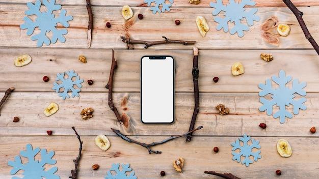 Smartphone entre ramitas y copos de nieve decorativos.