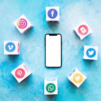 Smartphone rodeado de bloques de aplicaciones de medios sociales