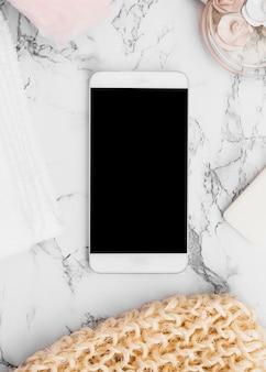 Smartphone rodeado de guante de matorral; jabón; botella de perfume; toalla y esponja sobre fondo de mármol