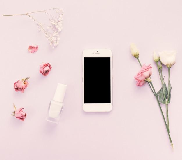Smartphone con rosas y esmalte de uñas en mesa