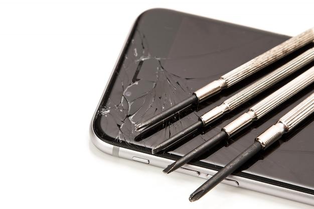 Smartphone roto y destornilladores pequeños para reparar