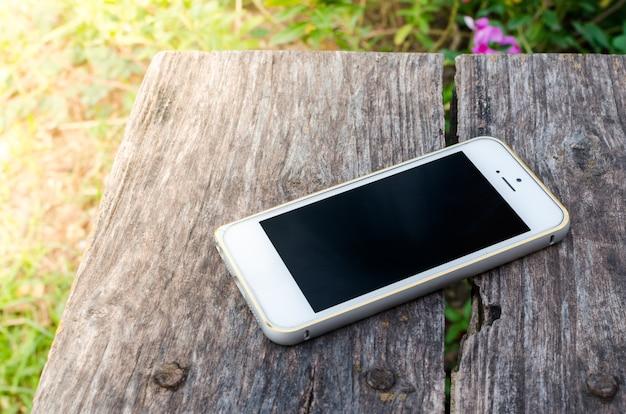 Smartphone sobre fondo de madera marrón antiguo en el jardín
