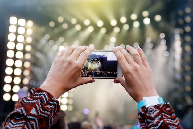 Smartphone sobre la multitud en un concierto de música. grabar espectáculo de luces