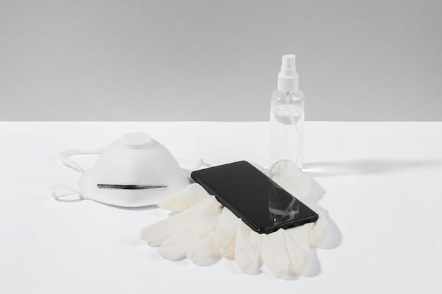 Smartphone en superficie con mascarilla y guantes quirúrgicos