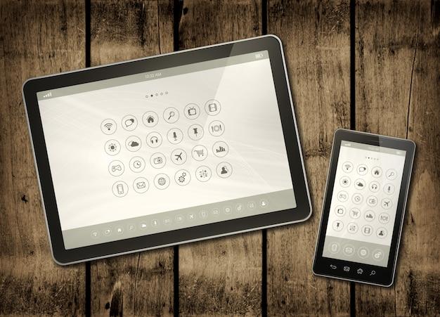 Smartphone y tableta digital con iconos de escritorio en una mesa de madera oscura