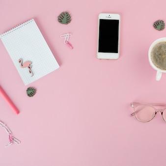 Smartphone con taza de café y bloc de notas en mesa rosa