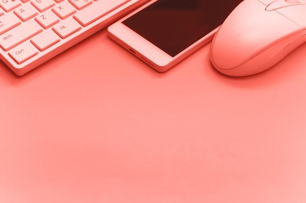 Smartphone, teclado, ratón sobre fondo de copia en color rosa en tonos.