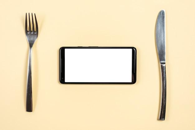 Smartphone entre el tenedor de acero inoxidable y el cuchillo de mantequilla sobre fondo beige.