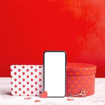 Smartphone vacío entre cajas de regalo