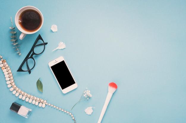 Smartphone con vasos, taza de té y flores.