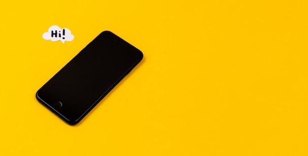 Smartphones con burbujas de discurso de papel sobre fondo amarillo. concepto de comunicación. vista superior. copia espacio composición de papel con texto hola
