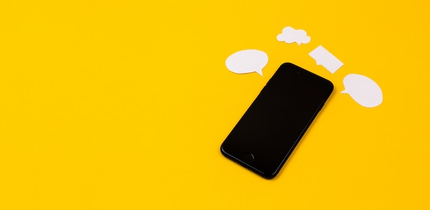 Smartphones con burbujas de discurso de papel sobre fondo amarillo. concepto de comunicación. vista superior. copia espacio composición de papel