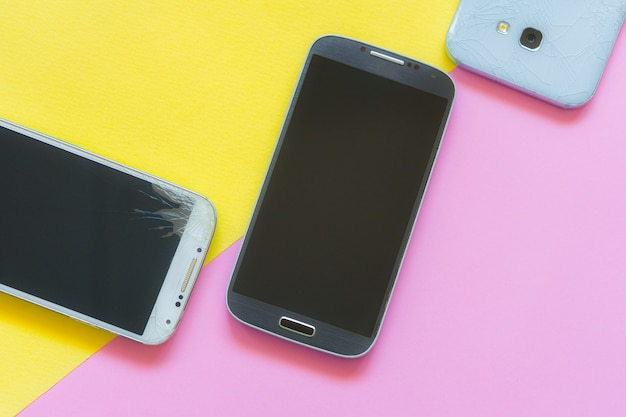 Smartphones móviles con pantalla de cristal roto aislado en rosa y amarillo. copyspace para texto. servicio, reparación y tecnología concepto plano lay. teléfono táctil roto