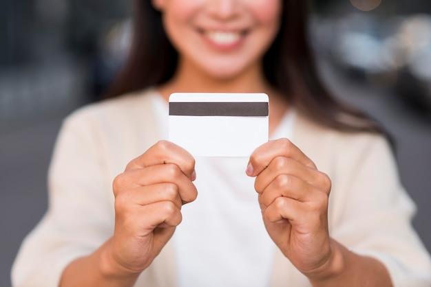 Smiley defocused mujer sosteniendo tarjeta de crédito