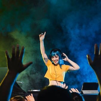 Smiley dj mujer divirtiéndose con multitud