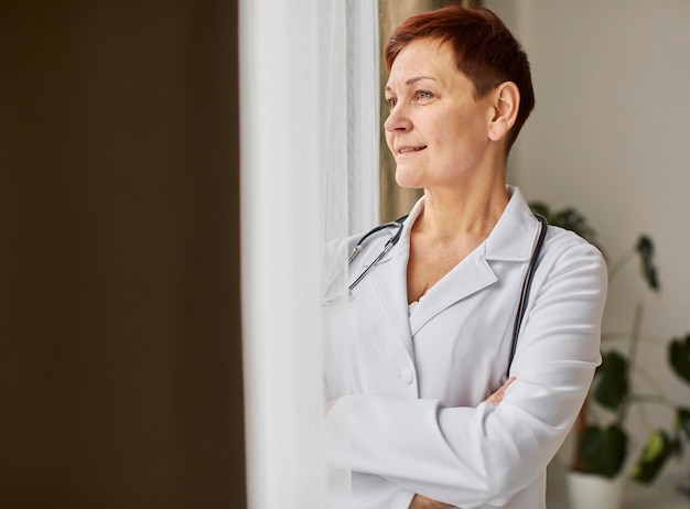 Smiley elder covid recovery center doctora mirando por la ventana