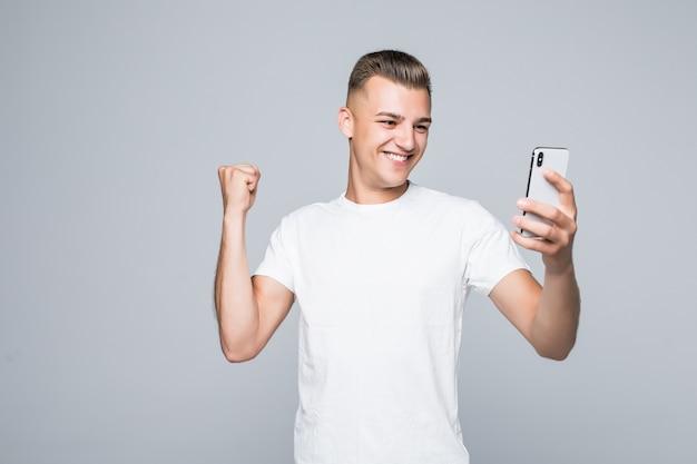 Smiley fuerte joven lleva una camiseta blanca y se está tomando un selfie con un teléfono inteligente plateado.