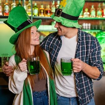 Smiley hombre y mujer celebrando st. patrick's day en el bar con bebida