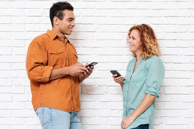 Smiley hombre y mujer con teléfonos